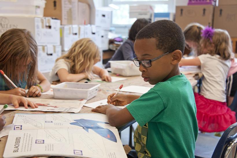 A Kid In School Writing Down