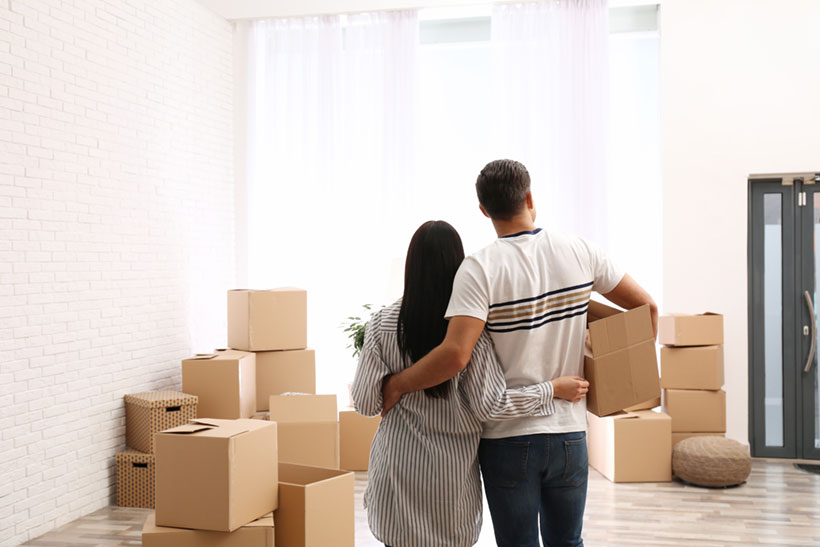 A Couple Looking at the Moving Boxes Before the Move