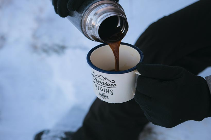 A Man Drinks Hot Coffee At The Snow