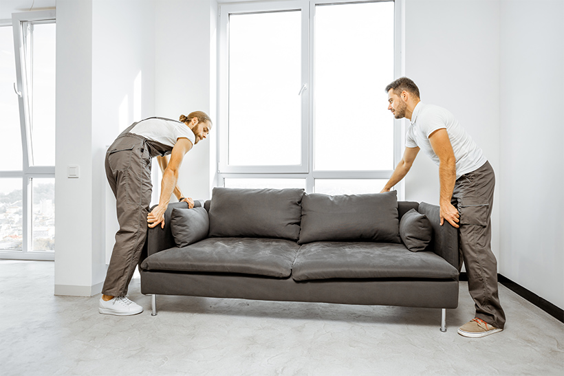 Two movers are moving a sofa